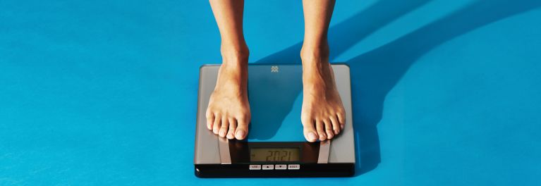 Feet on a clear Weight Watchers body-fat scale