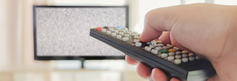 A person pointing a reomote at their TV—trying to fix the HDTV soap opera effect.