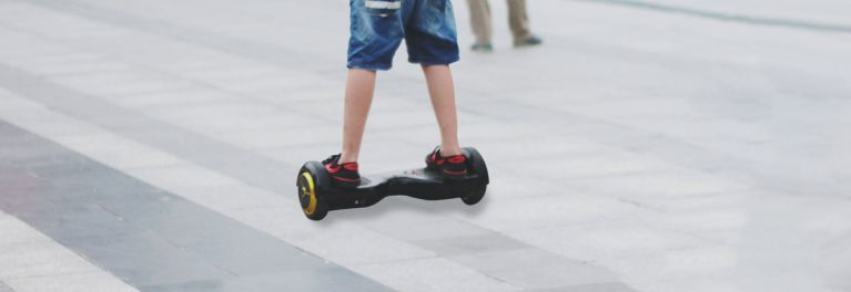 Photo of a youth astride a hoverboard on a sidewalk