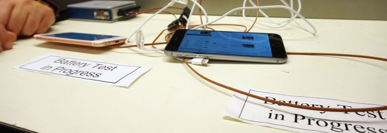 Two iPhone 6s smartphones on a table, hooked up to tiny, adhesive-backed heat sensors called thermocouples, which continually feed their readings to a small module connected to a computer via a USB cable.