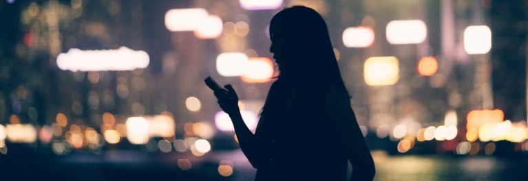 Smartphone hacking illustrated by a dark photo of a woman holding a phone