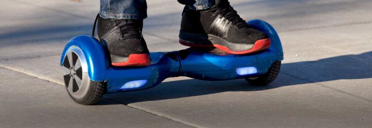 a child's feet on a blue hoverboard for a story on a major hoverboard recall