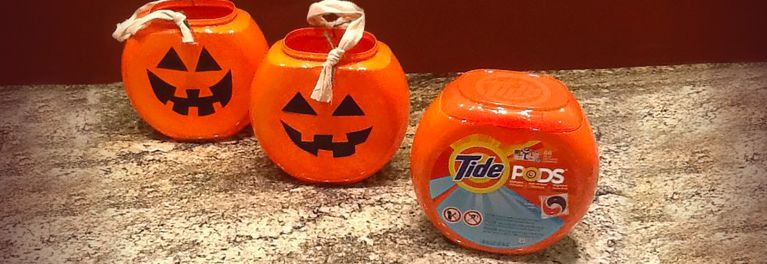 Laundry pod containers made into jack-o-lantern buckets.