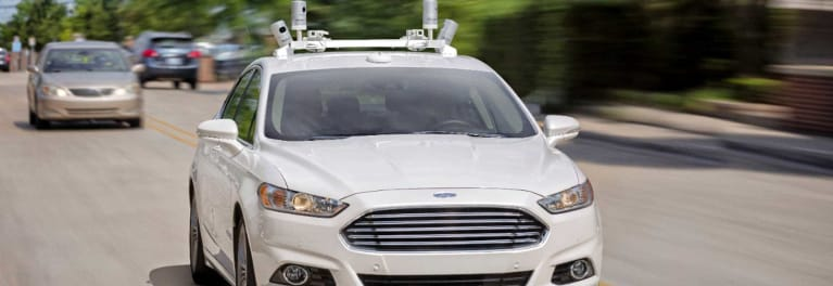 A photo of a Ford test vehicle equipped with roof-mounted cameras for autonomous driving.