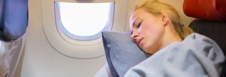 A woman sleeping on a plane, which might worsen jet lag.