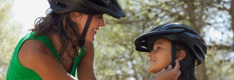 Women wearing a bike helmet helping a child get the right bike helmet fit.