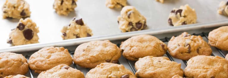 An image of baked cookies with raw cookie dough, which the FDA warns uncooked cookie dough shouldn't be eaten due to the risk of e.coli contamination in flour.