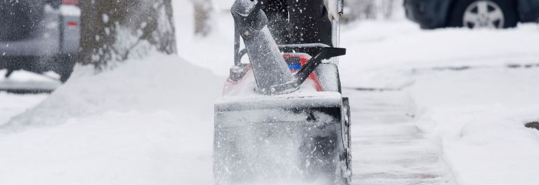 Using a snow blower to clear a sidewalk.