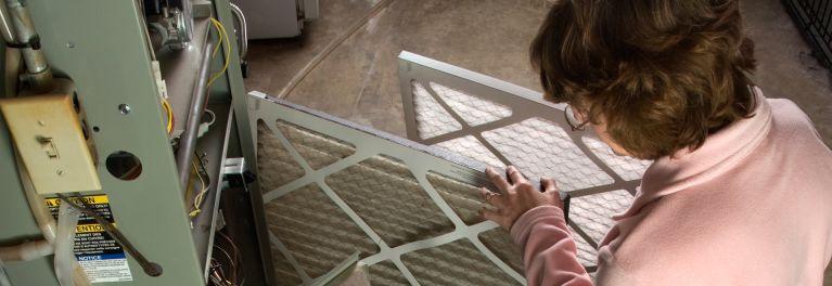 Homeowner replacing a furnace filter.