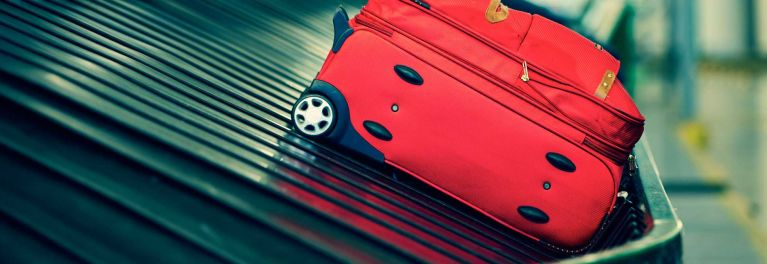 Red luggage on an airport carousel.
