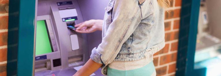 A college co-ed accesses her student checking account at an ATM.