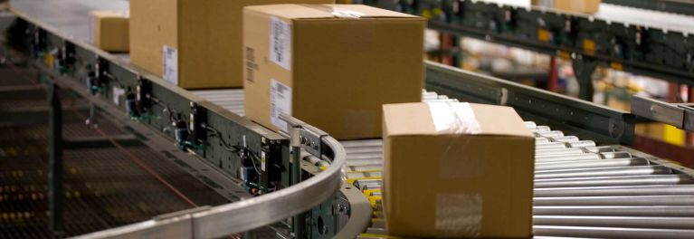 A photo of a conveyor belt expediting packages to meet holiday shipping deadlines are met.