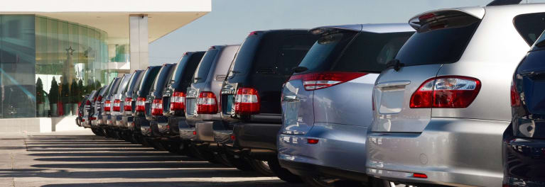 Pros and Cons of Car Leasing - A photo of a row of brand-new minivans and SUVs.