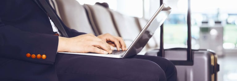 airline laptop ban and how to encrypt a laptop shown by a business traveler working in an airport