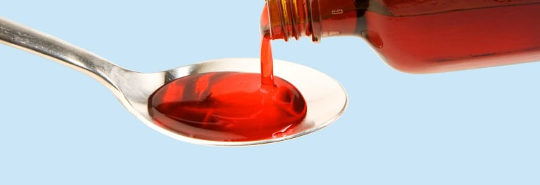 Cough medicine containing codeine is poured into a spoon.