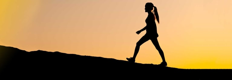 Woman walking uphill. There are many health benefits of walking.