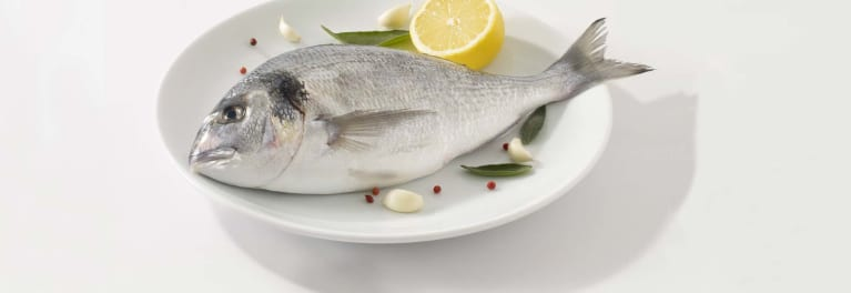 A large fish on a plate. Fish is a longevity food.