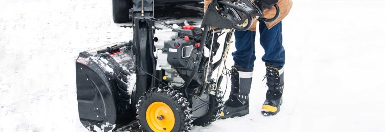 A person using a large snow blower to clear snow.