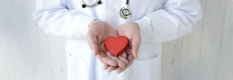 Heart disease: A doctor holds a wooden heart.