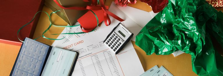 A calculator and credit card bill on top of holiday wrapping paper