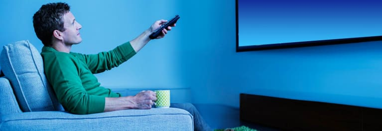 Photo of a man watching a smart TV that is capable of TV snooping.