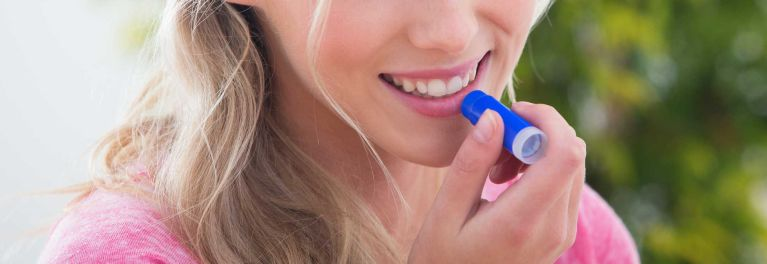 Woman applying a lip balm with SPF.