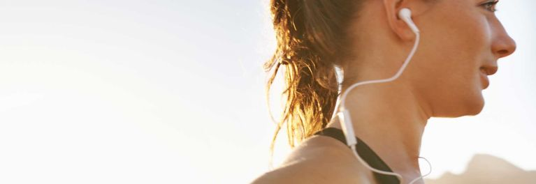 A woman wearing white headphones, for a story on music streaming services