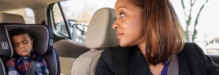 A woman in a car looking back at her child in a car seat.