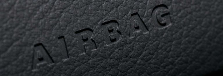 A close-up image of airbag embossed on a car's steering wheel.