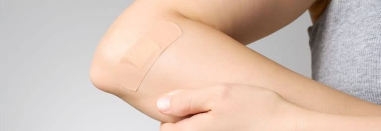 A bandage on an arm. How to safely remove skin tags and other growths.