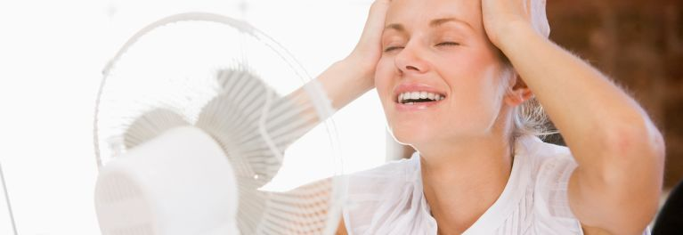 Woman with a menopause hot flash, for which black cohosh is recommended,  in front of a fan suggesting