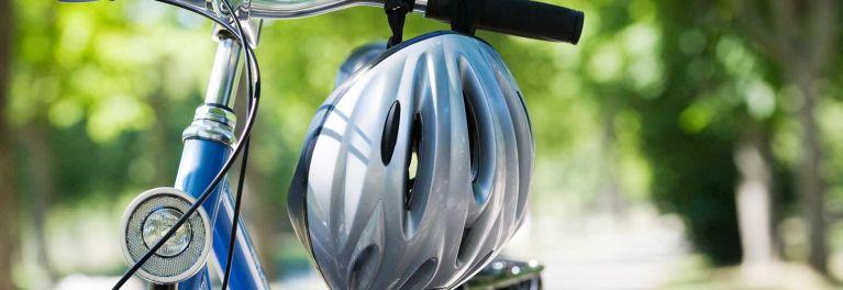 A bike helmet hanging on a bike handlebars. Bike helmets may help protect against concussions.