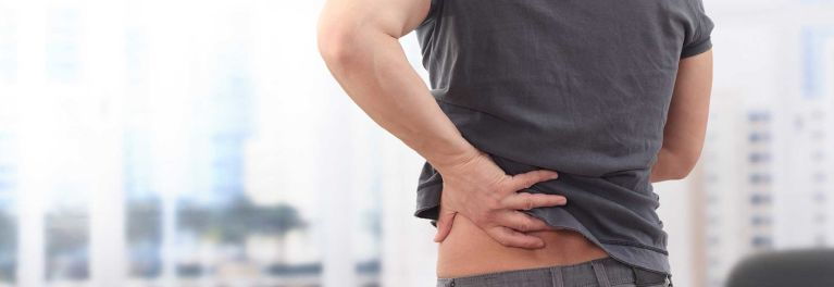 Low Back Pain: Man with hand on painful back