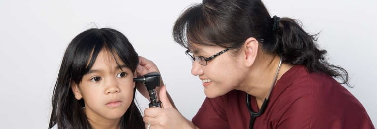 A health professional examining a child's ear
