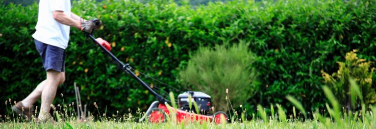 A man mowing his lawn with a push mower for an article on lawn mowers for every budget.