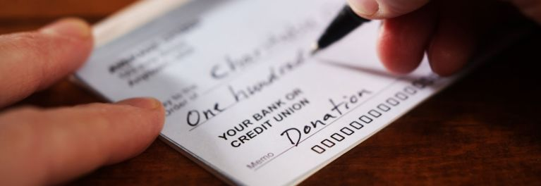 A person writing a check to a charity
