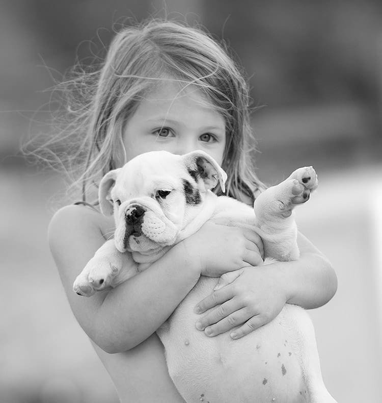 A young girl holding a puppy.