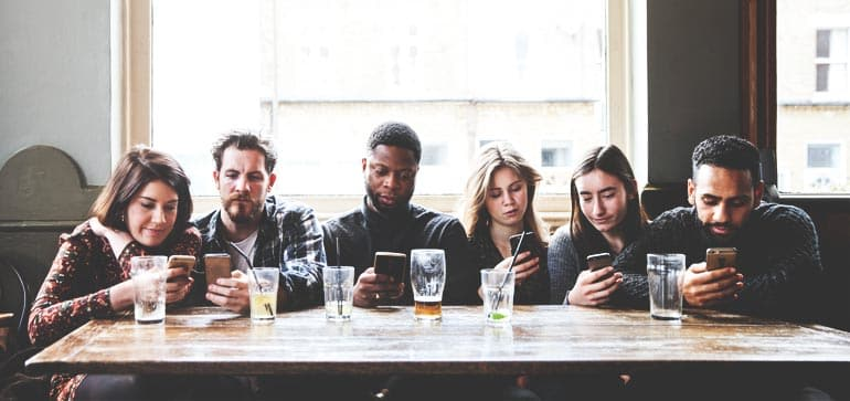 A group of friends on their phones in a bar, possibly choosing among cell-phone companies