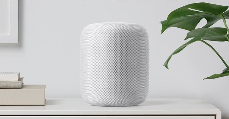 The Apple HomePod speaker sitting on a desk.