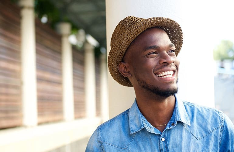 A smiling man wearing a hat.