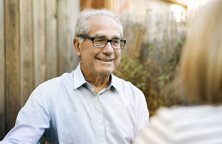 An older man smiling.