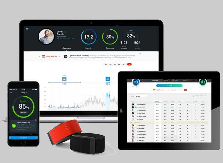 Two Whoop Strap waterproof fitness bands placed in front of a phone and tablet with the tracker's app.