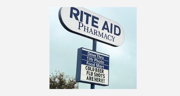 A photo of a Rite Aid Pharmacy store sign that says cold beer and flu shot are available at this location.