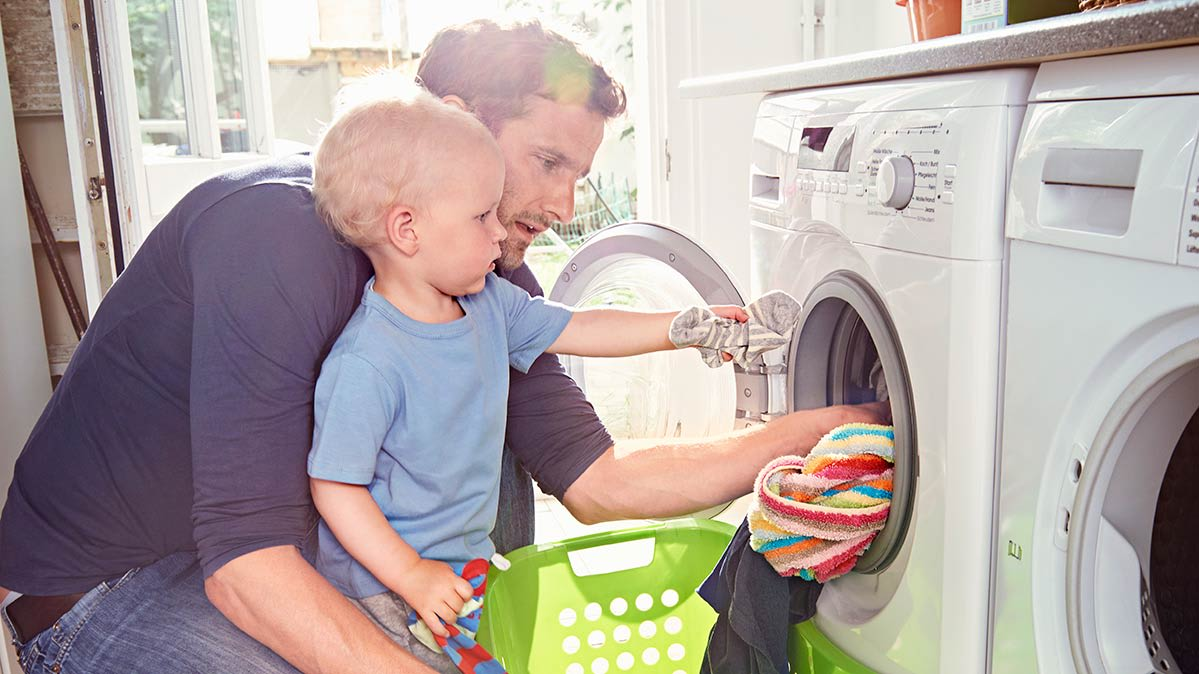 A man and a young child in front of a washer and dryer set