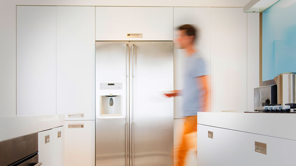 A man walking past a side-by-side refrigerators.