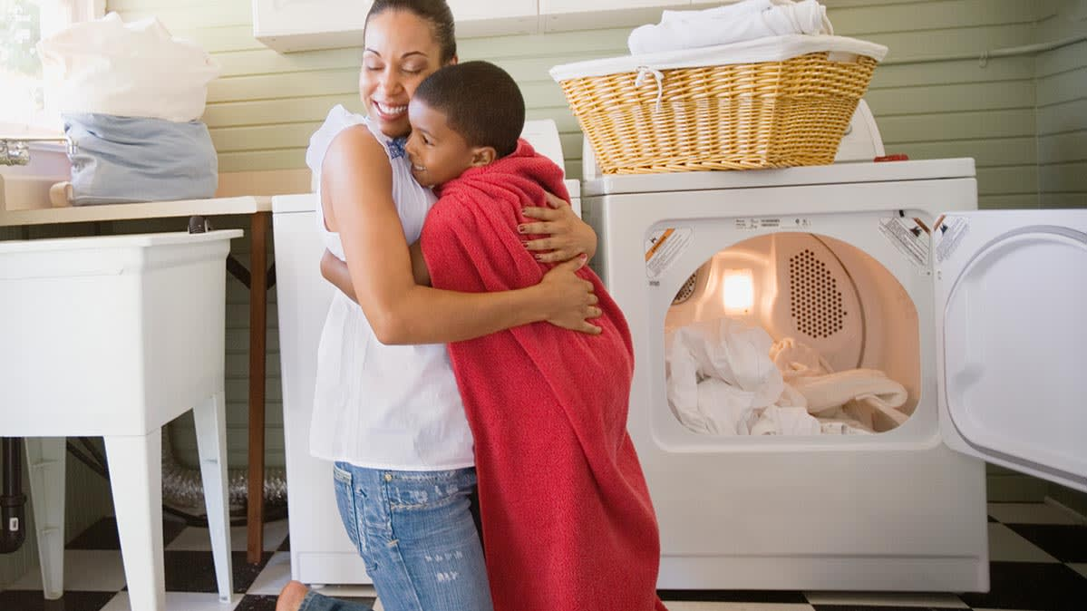 A mom hugging her son in front of a clothes dryer.