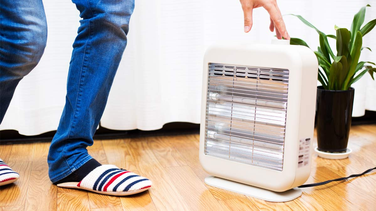 A person reaching down to a space heater on the floor