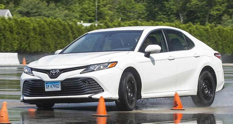 Car tires undergoing wet handling tests at Consumer Reports' test track