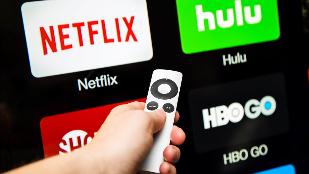 Person using a remote control to find streaming shows and movies.