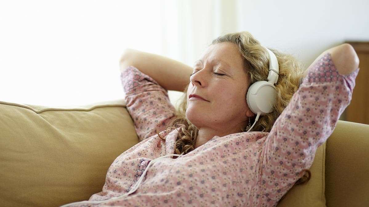 A woman on a sofa wearing headphones to listen to music streaming.